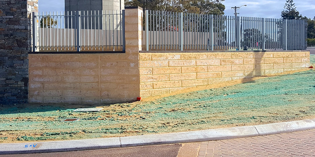 residential limestone retaining wall Perth based in joondalup. Grass out front and fencing onto of the limestone